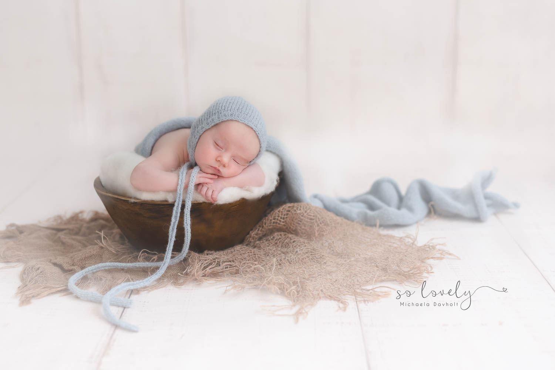 nyfödd ligger i en korg med mössa på huvudet