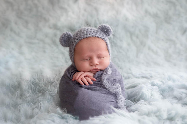 liten och nyfödd insvept i filt och mössa på huvudet